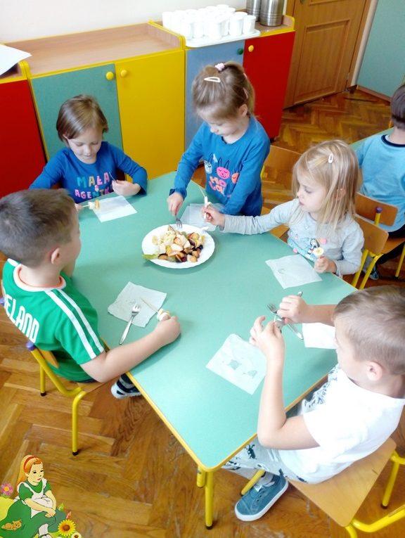 Dzieci siedzą przy stoliku, nadziewają owoce na patyki do szaszłyków