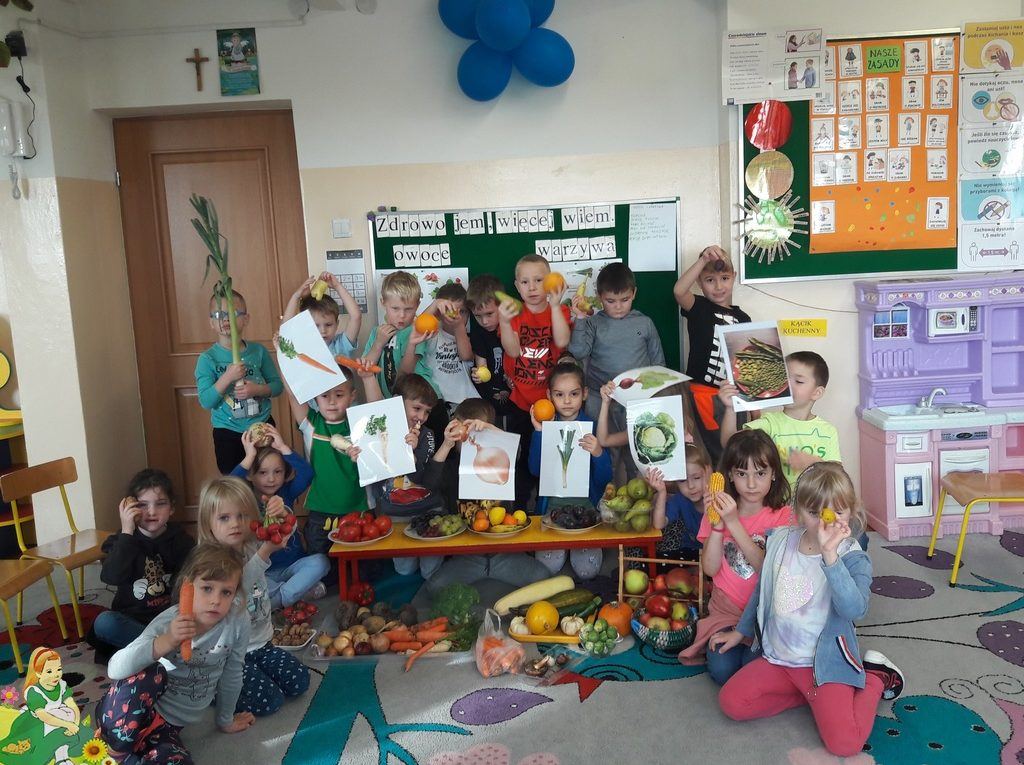 Dzieci w grupie pokazują zgromadzone owoce i warzywa.