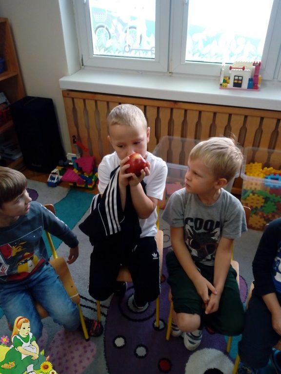 Troje chłopców, jeden wącha jabłko