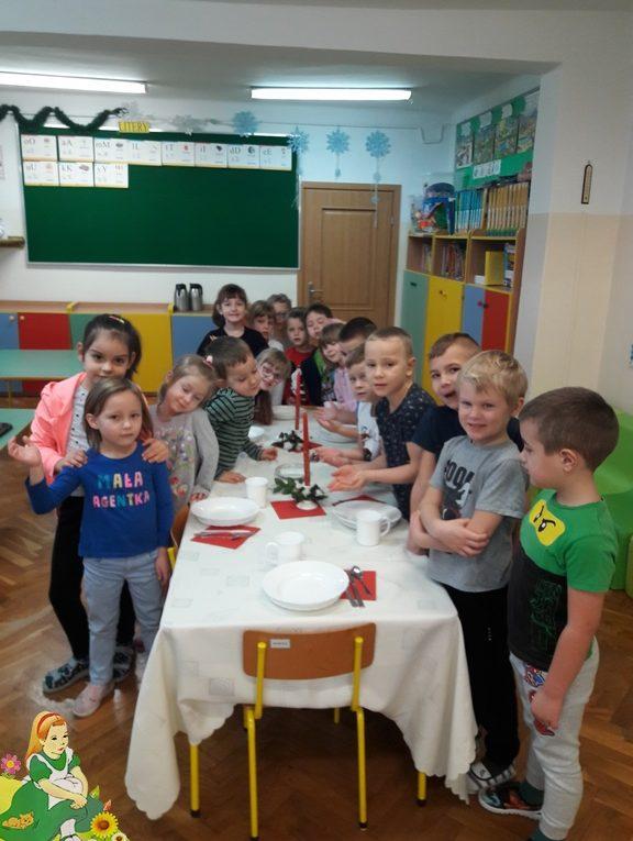 Dzieci stoją naokoło nakrytego i przystrojonego stołu.