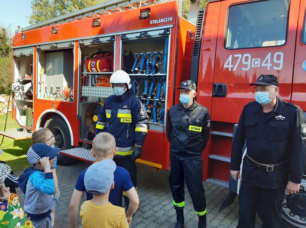 Strażacy przy wozie strażackim opowiadają dzieciom o swojej służbie.