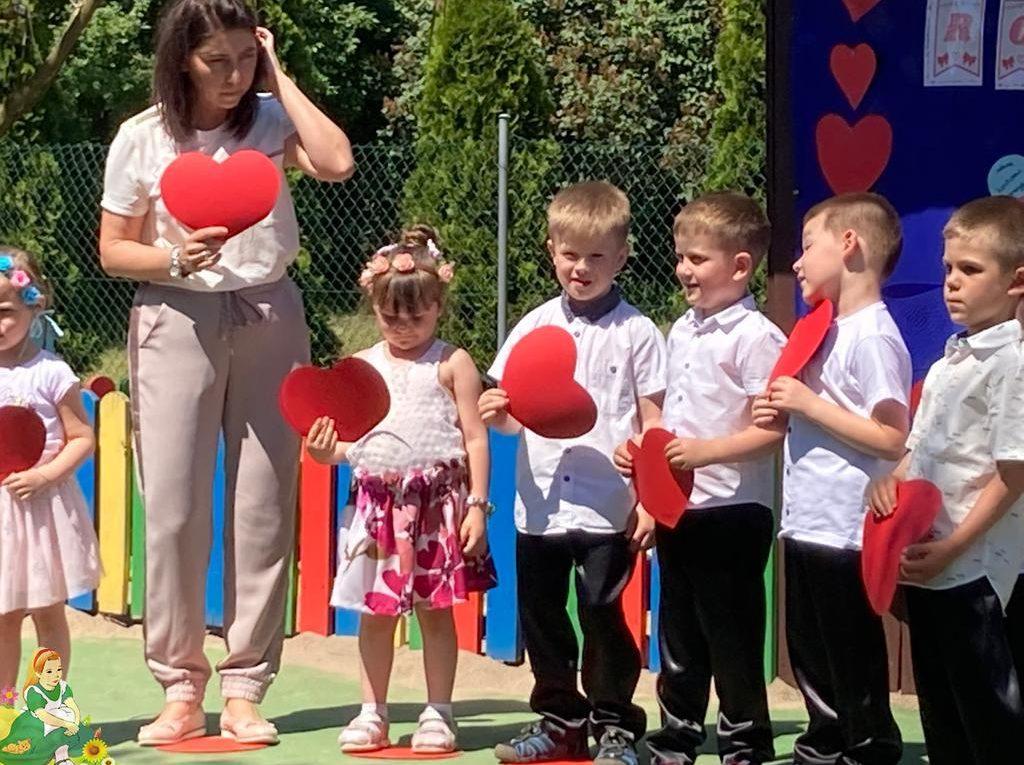 Dzieci stoją z panią podczas występu, trzymają czerwone serca.