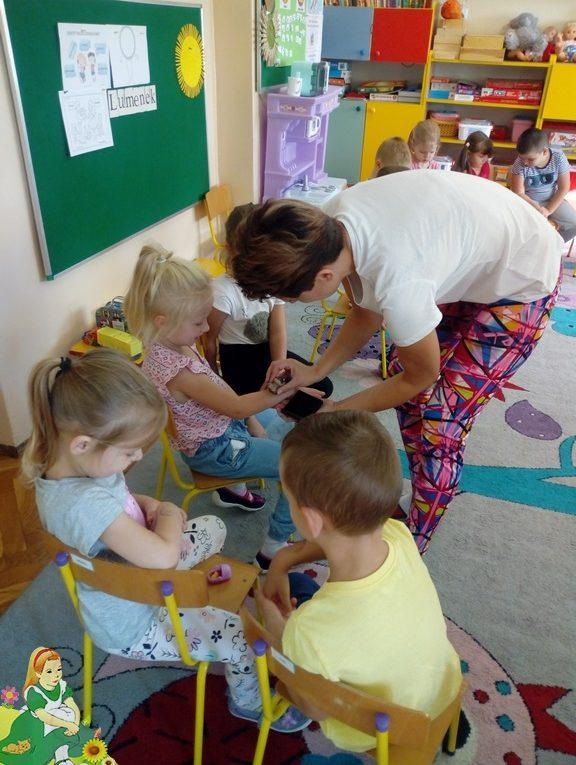 Nauczycielka stawia dzieciom uśmiechnięte pieczątki na prawej ręce