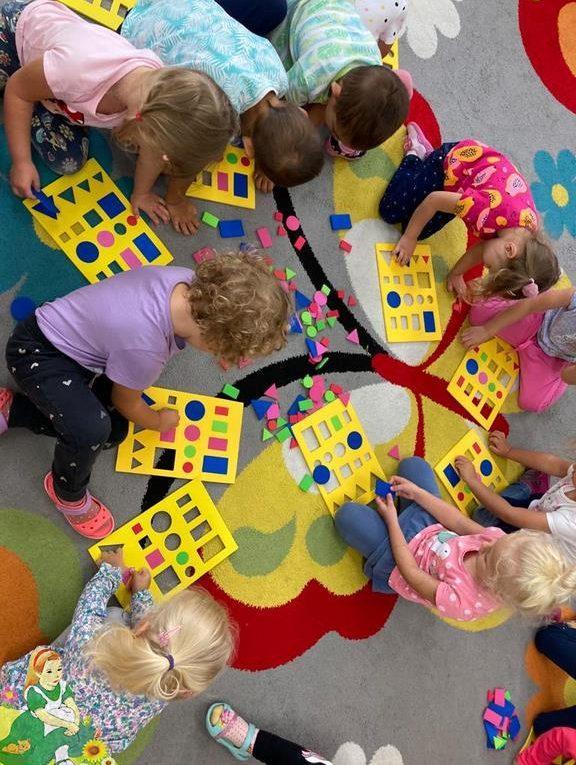 Dzieci na dywanie układają figury geometryczne