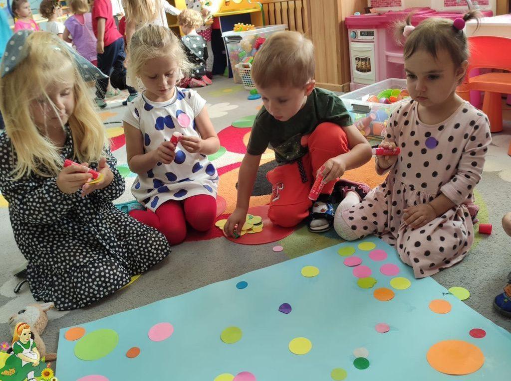 Dzieci kleją obraz z kropek