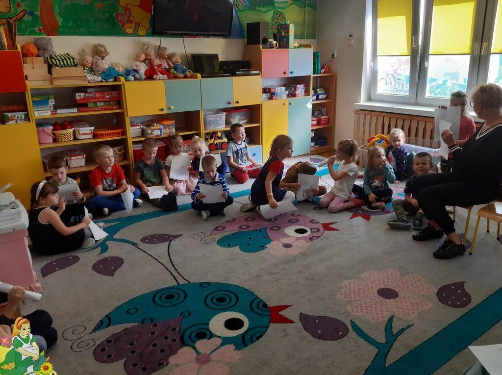Dzieci siedzą w kole na dywanie z paniami prowadzącymi.