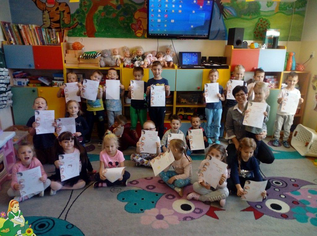 Dzieci z grupy Leśne Skrzaty pokazują rysunki uśmiechniętej buźki, którą same narysowały